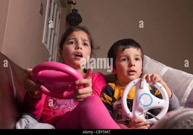 Siblings playing computer game at home - Stock Image