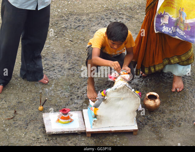 A young boy performs the traditional ritual of Lord Ganesh during Ganesh festival. - Stock-Bilder