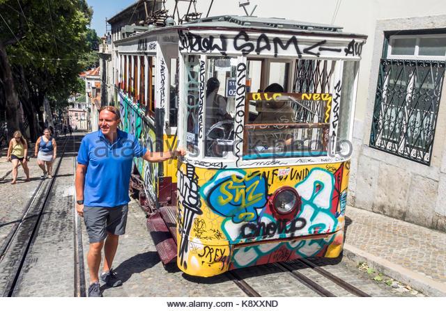 Portugal Lisbon Bairro Alto Elevador da Gloria ascensor funicular railway tram Carris graffiti man posing - Stock Image