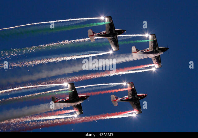 The Pioneer Team flying their Alpi Aviation Pioneer 300 aircraft in an aerobatic display at dusk - Stock Image