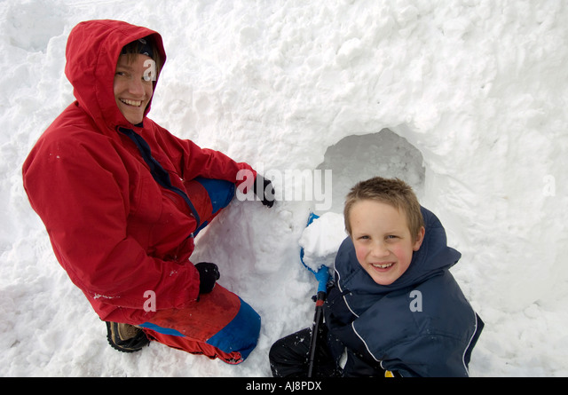 Mother and son dig a snow cave. - Stock Image