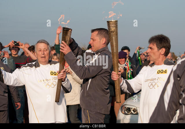 Falmouth, UK. 19 May, 2012. Eric Smith hands the Olympic torch to Steve Brady. - Stock Image