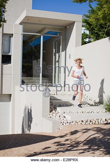 Woman leaving house to jog - Stock-Bilder