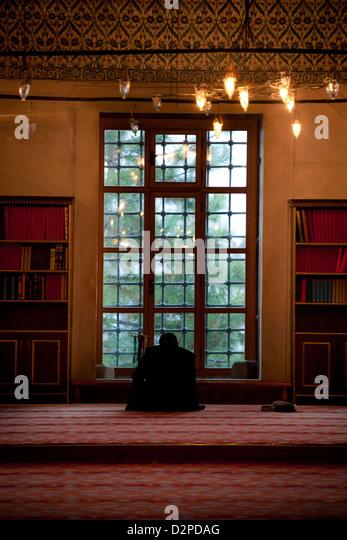BLUE MOSQUE ( Sultan Ahmet Camii ): muslim man praying by the window while outside snowing, Sultanahmet Istanbul - Stock Image