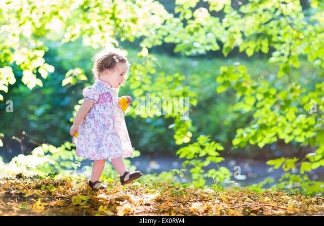 Beautiful baby girl in a pink dress walking next to a river on a very sunny warm autumn day - Stock Image