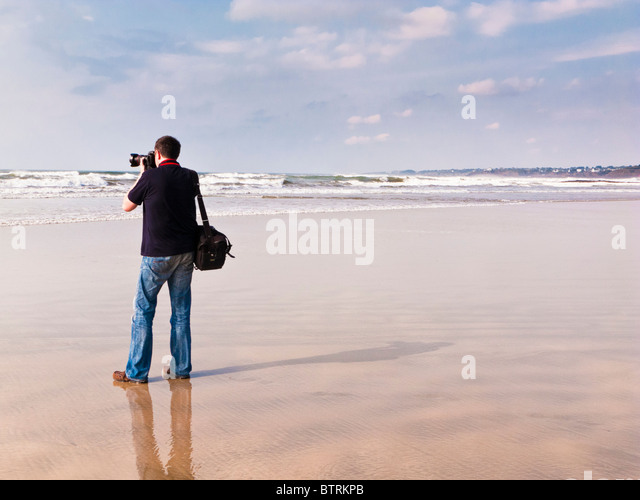 Photographer on a deserted beach shooting the ocean France Europe - Stock Image