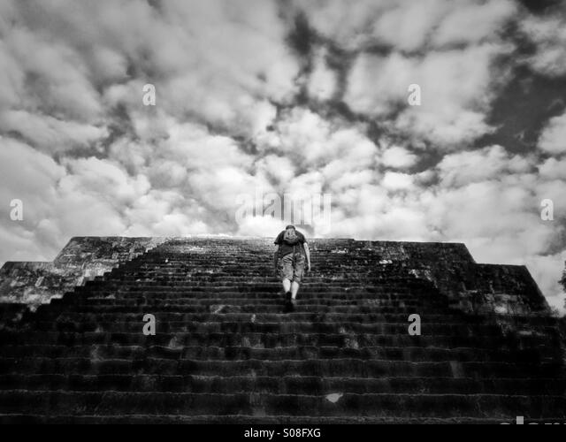 Man climbing pyramid at Tikal, Guatemala - Stock Image