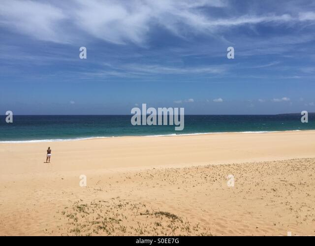 Lone beach walk - Stock Image