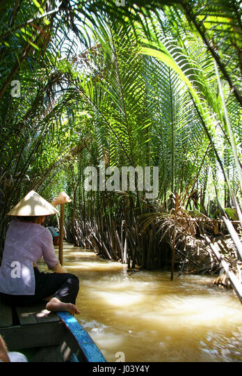 This Vietnamese woman paddles tourists through the back channels of the Mekong Delta. - Stock Image