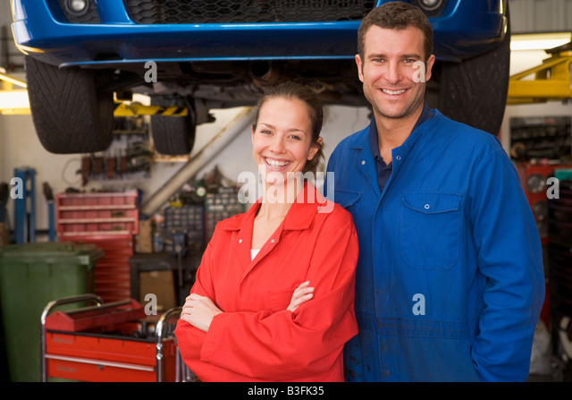 Two mechanics standing in garage smiling - Stock Image