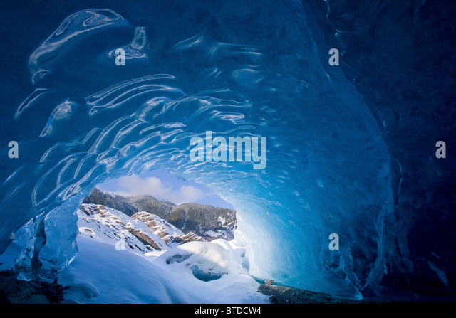 View from inside an ice cave looking outward at the snowcovered landscape, Mendenhall Glacier near Juneau in Alaska, - Stock Image