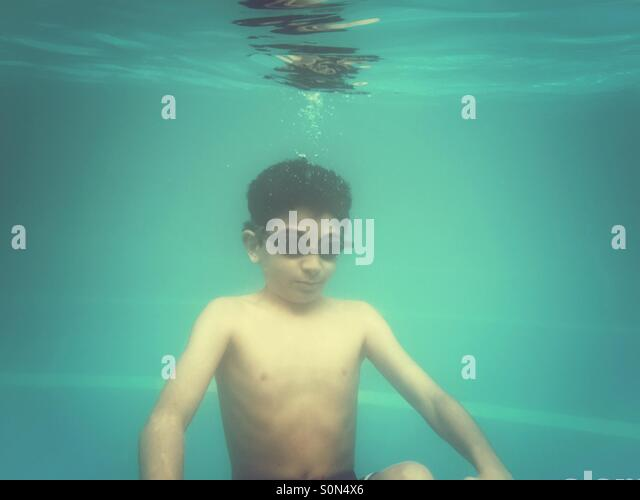 10 years old boy swimming underwater in the pool - Stock Image
