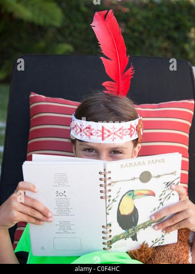 Girl wearing indian feather peeking over book - Stock Image