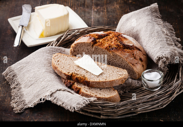 Rye sliced bread and butter on wooden table - Stock Image