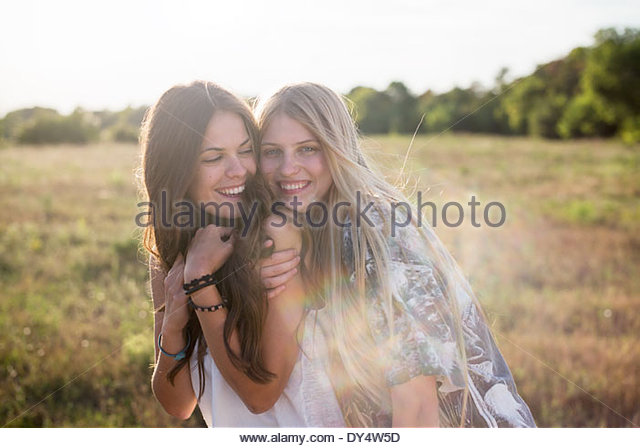 Two young women with long hair in field - Stock Image