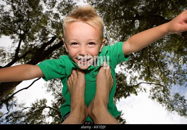 Smiling Young Boy balancing on feet - Stock-Bilder