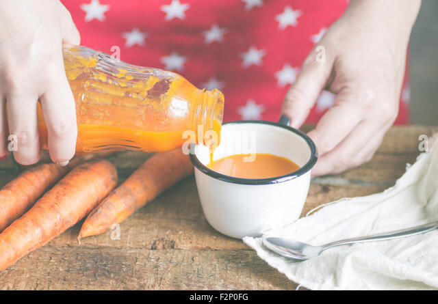 The woman pours a bottle of carrot juice in a mug - Stock-Bilder