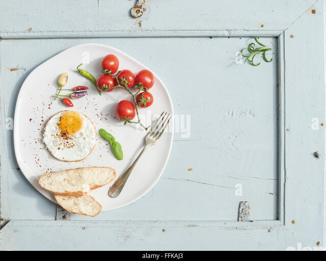Breakfast set. Fried egg, bread slices, cherry tomatoes, hot peppers and herbs on white ceramic plate over light - Stock Image
