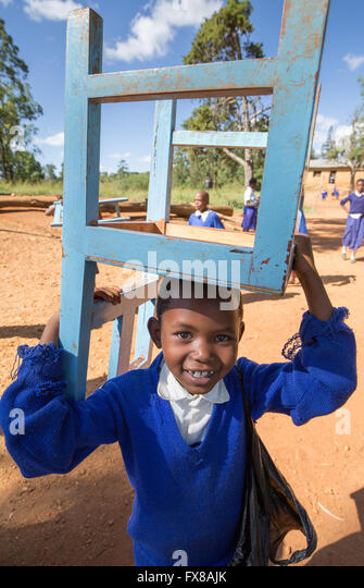 Smiling Kenyan schoolboy carrying a chair back to the classroom of a school in the Sagalla Hills of Southern Kenya - Stock Image