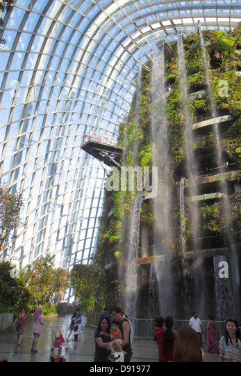 Singapore Gardens by the Bay park Cloud Forest mountain greenhouse waterfall Asian family man woman father mother - Stock Image