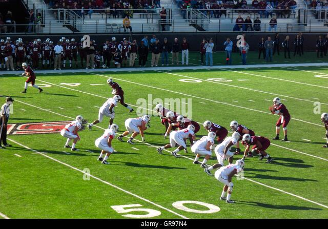 American Football Players Playing In Stadium - Stock Image