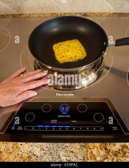 Magnetic energy of touching touch energy saving Thermador Induction cooktop with melting cheese  MR  © Myrleen - Stock-Bilder