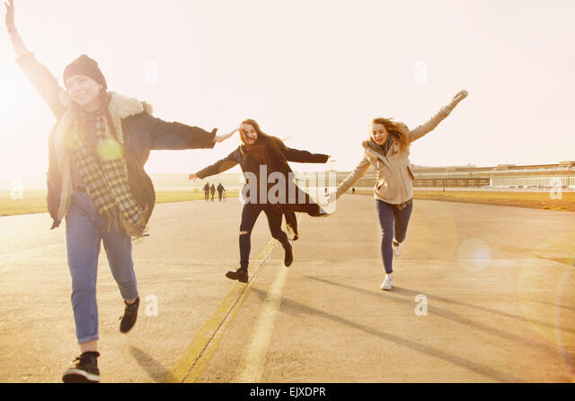 Teenage Girls Running with Arms Outstretched - Stock Image