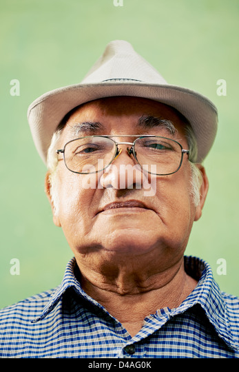 people and emotions, portrait of serious senior hispanic man with glasses and hat looking at camera against green - Stock Image