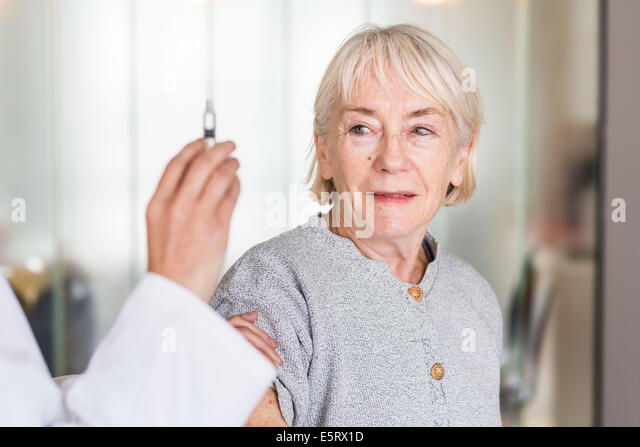 Woman receiving vaccination. - Stock Image