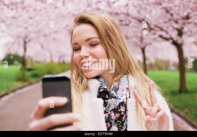 Pretty young female model gesturing peace sign while taking her picture with cell phone. Beautiful caucasian young - Stock-Bilder