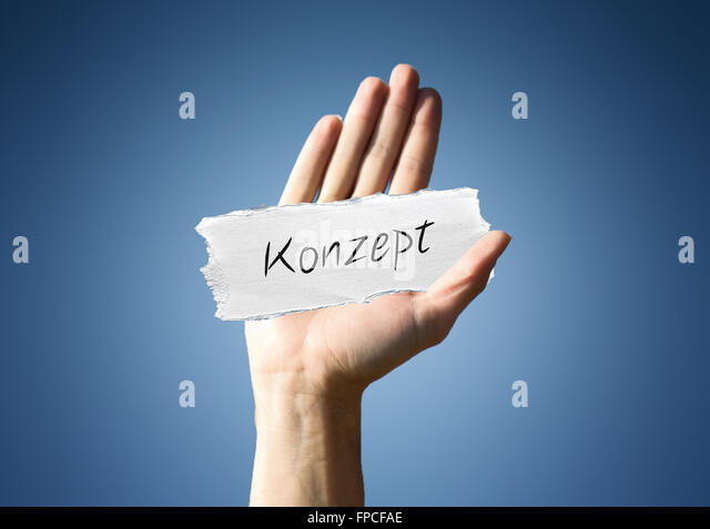 man holding up a scrap of white paper with the german word - Konzept - in script, close up of his hand on a blue - Stock-Bilder
