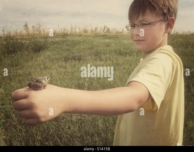 A boy holds a frog on his hand. - Stock Image