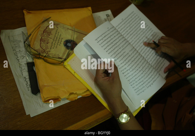 Tibetan Buddhist Monk Jigme Wanggyal edits a history book he wrote about the history religion in India and how Buddhism - Stock Image