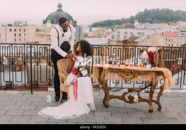 Gorgeous newlyweds softly holding hands on the terrace - Stock Image