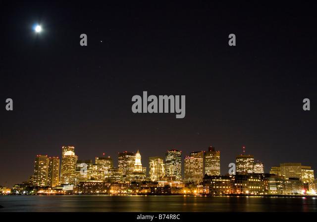Boston skyline on a moonlight starry night with Boston Harbor in the foreground Massachusetts USA - Stock Image