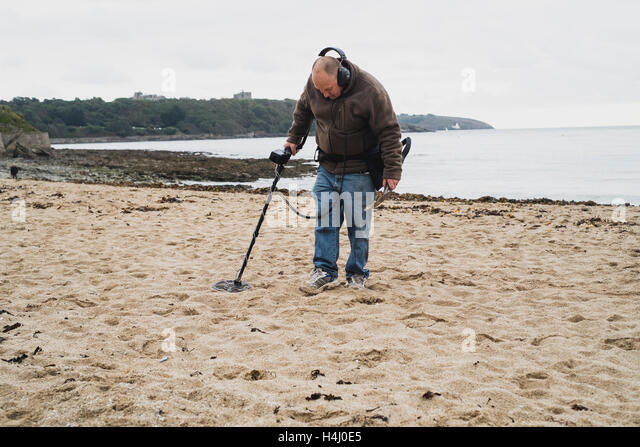 A man with a metal detector working on Falmouth's Gyllyngvase Beach - Stock Image