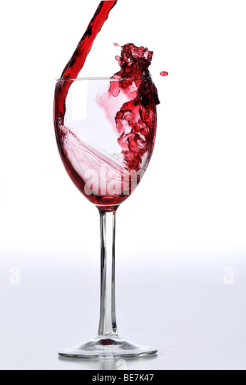 Red wine poured on glass isolated against a white background - Stock-Bilder