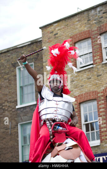 Carnival in Hackney a black man holds a baton like a Roman soldier wearing a costume of body armour and a flaming - Stock Image