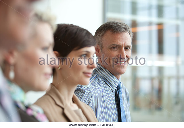 Smiling businessman in row of business people - Stock Image