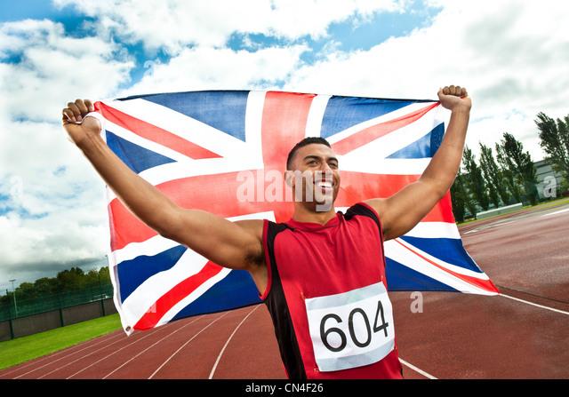 Sprinter holding Union flag on sportstrack - Stock Image
