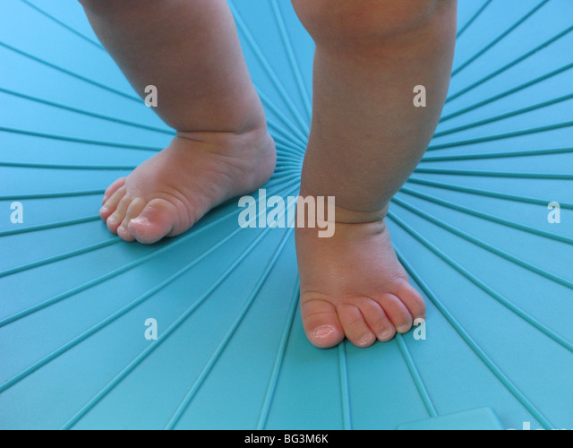Legs and feet of an infant learning to walk in a blue environment - Stock Image