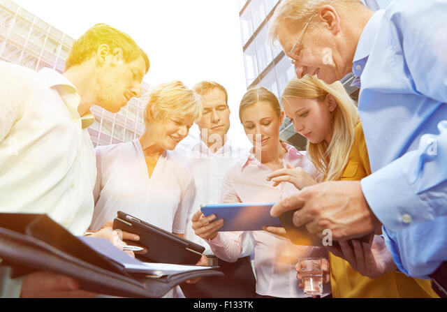 Business meeting with tablet computer in summer on a sunny day outdoors - Stock Image