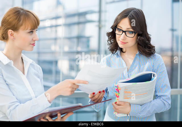 Businesswoman showing document to female colleague in office - Stock Image