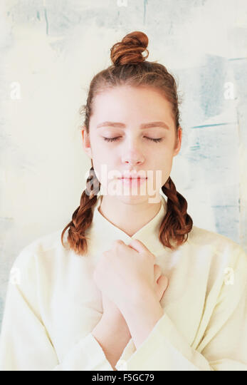 The quiet girl stands with closed eyes and folded hands - Stock-Bilder