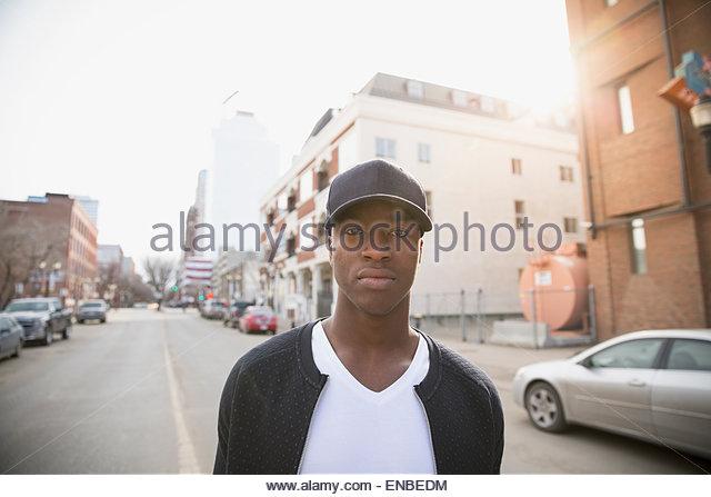 Portrait serious man in baseball cap urban street - Stock Image