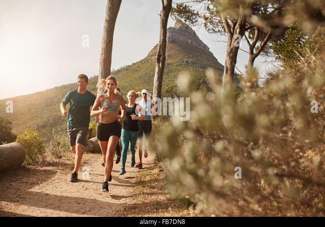 Group of young adults training and running together through trails on the hillside outdoors in nature. Fit young - Stock Image