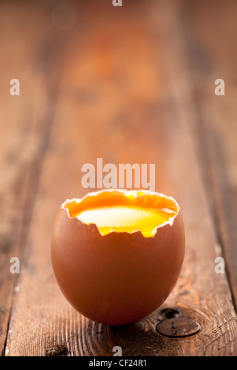 Opened Egg Shell with Yolk on Wood - Stock-Bilder