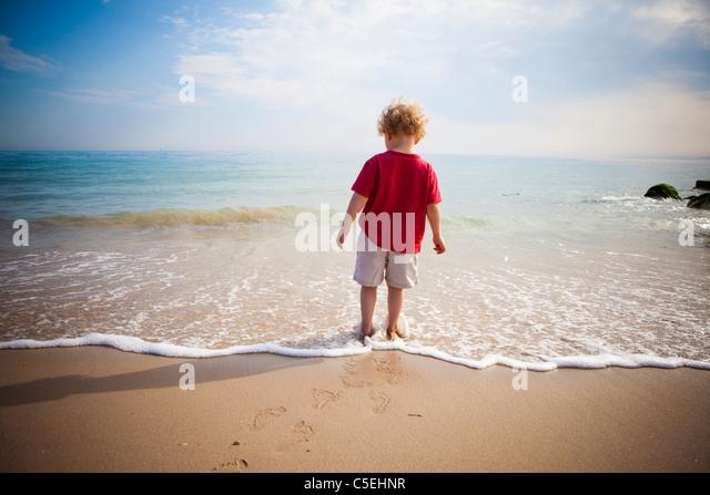 Boy standing in the sea - Stock-Bilder