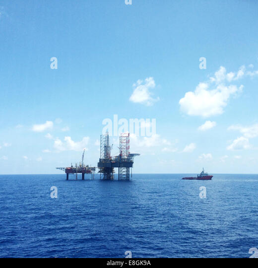 Oil and gas platform with offshore vessel transporting cargo - Stock-Bilder
