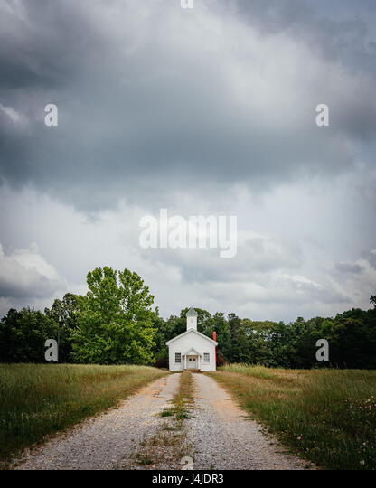 A small white church sits at the end of a dirt road, in a field, in rural central Alabama. - Stock Image